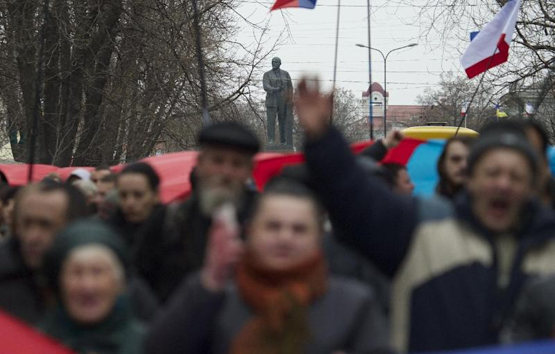 A statue of Soviet founder Vladimir Lenin in background as local residents carry giant Russian flags and shout slogans while rallying on the streets of Simferopol, Ukraine, on Saturday, March 1, 2014. Russian President Vladimir Putin asked his parliament Saturday for permission to use the country's military in Ukraine, moving to formalize what Ukrainian officials described as an ongoing deployment of Russian military on the country's strategic region of Crimea. (AP Photo/Ivan Sekretarev)