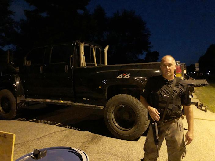 Tim Pinter guards the entrance to his neighborhood with a semiautomatic rifle.
