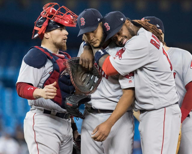 Boston Red Sox starting pitcher Eduardo Rodriguez gets a hug from teammate Hanley Ramirez as he waits for his manager to take him out of the game in the seventh inning baseball action in Toronto on Wednesday April 25, 2018. (Fred Thornhill/The Canadian Press via AP)