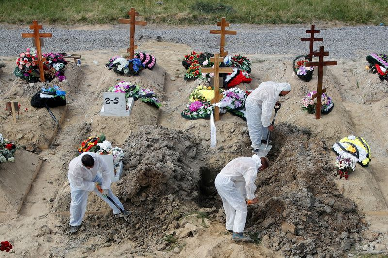 FILE PHOTO: Grave diggers wearing personal protective equipment bury a person at a graveyard in Saint Petersburg