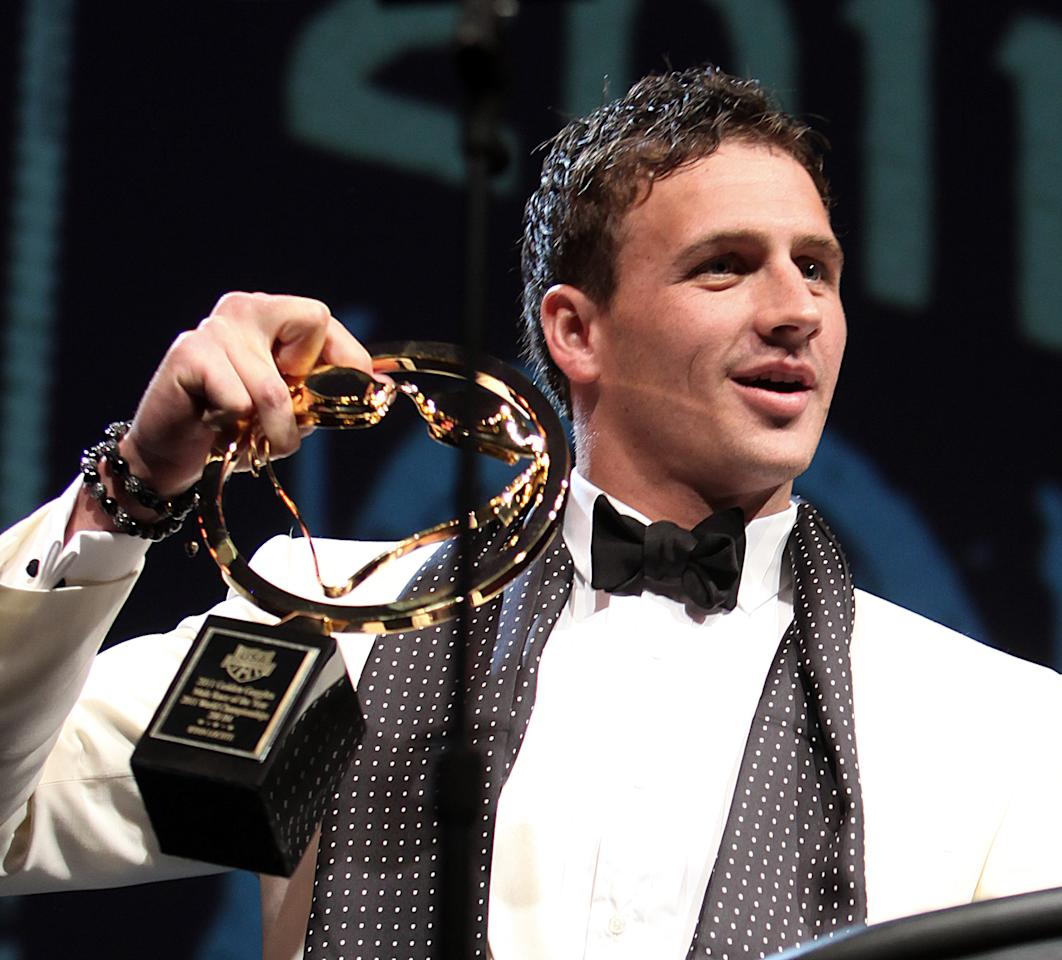 After knocking the award off the podium and grabbing it before it hit the floor, Ryan Lochte holds the award for best male race of the year at the USA Swimming Foundation's Golden Goggle awards in Los Angeles Sunday, Nov. 20, 2011. (AP Photo/Reed Saxon)