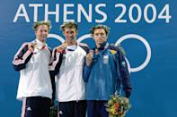 <p>Gold medalist Michael Phelps (center) shows off his gold medal for the men's swimming 100-meter butterfly event on August 20, 2004 in Athens. (Shaun Botterill/Getty Images)</p>
