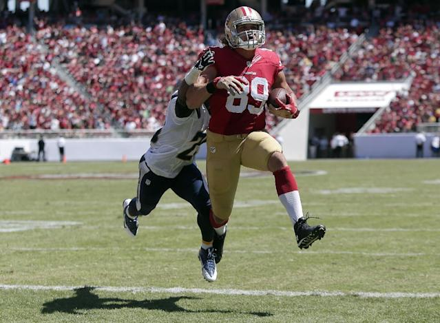 San Francisco 49ers tight end Vance McDonald (89) scores on a 6-yard touchdown reception in front of San Diego Chargers defensive back Darrell Stuckey during the second quarter of an NFL preseason football game in Santa Clara, Calif., Sunday, Aug. 24, 2014. (AP Photo/Marcio Jose Sanchez)