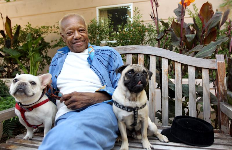 """In this June 22, 2012 photo, musician Bobby Womack sits with his dogs, a French bull dog named Music, left, and a pug named Wo in Los Angeles. With health and drug problems behind him, Womack makes his return with a new album, """"The Bravest Man in the Universe."""" (Photo by Matt Sayles/Invision/AP)"""