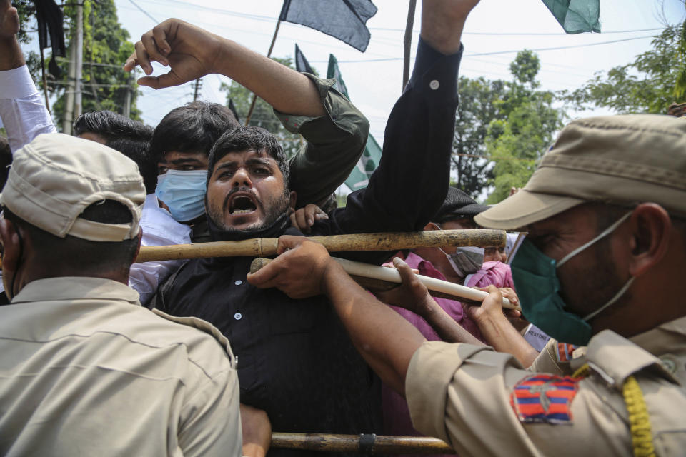 Activists of Peoples Democratic Party scuffle with police during a protest marking the second anniversary of Indian government scrapping Kashmir's semi- autonomy in Jammu, India, Thursday, Aug.5, 2021. On Aug. 5, 2019, Indian government passed legislation in Parliament that stripped Jammu and Kashmir's statehood, scrapped its separate constitution and removed inherited protections on land and jobs. (AP Photo/Channi Anand)