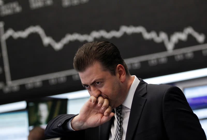 FILE PHOTO: Trader reacts at his desk in front of the DAX board at the Frankfurt stock exchange