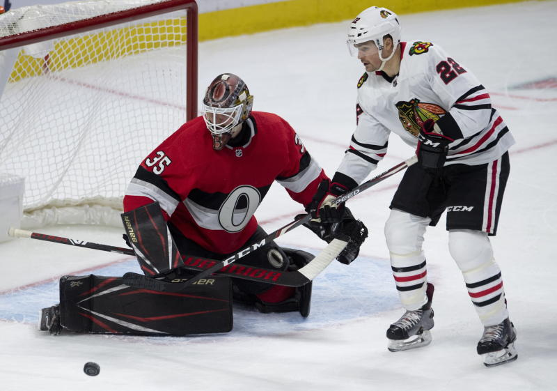 Chicago Blackhawks center Ryan Carpenter (22) tries to corral a loose puck in front of Ottawa Senators goaltender Marcus Hogberg during second period NHL hockey action in Ottawa, Tuesday, Jan. 14, 2020. (Adrian Wyld/The Canadian Press via AP)