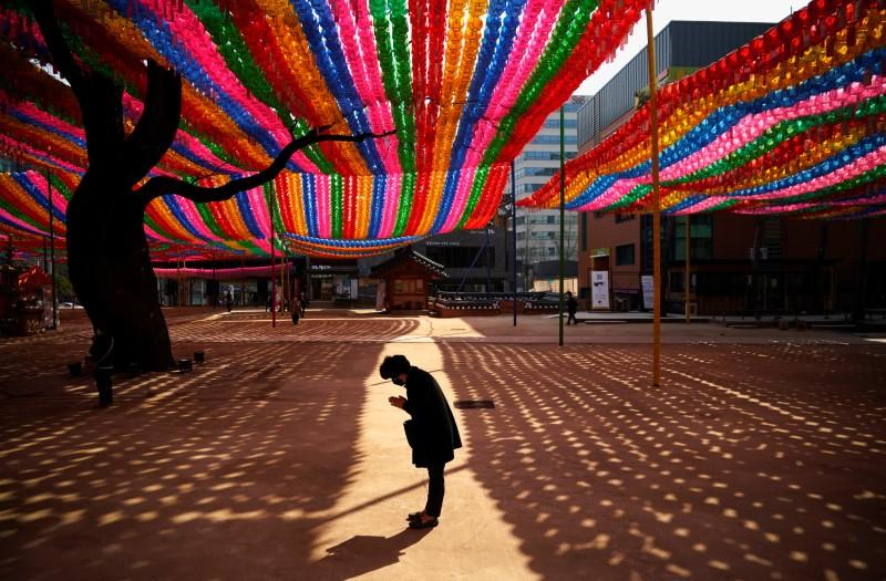 Buddhist believer wearing a face mask to prevent contracting the coronavirus disease (COVID-19) prays under colorful lanterns in preparation of the upcoming birthday of Buddha at a temple in Seoul,