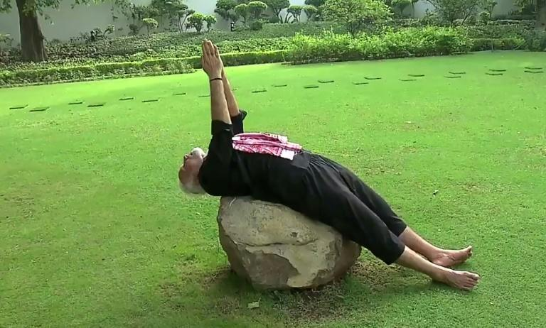 In one clip Modi, clad in a black tracksuit, walks backwards over a treaded lawn with his hands clasped in a prayer pose, before stretching over a large boulder