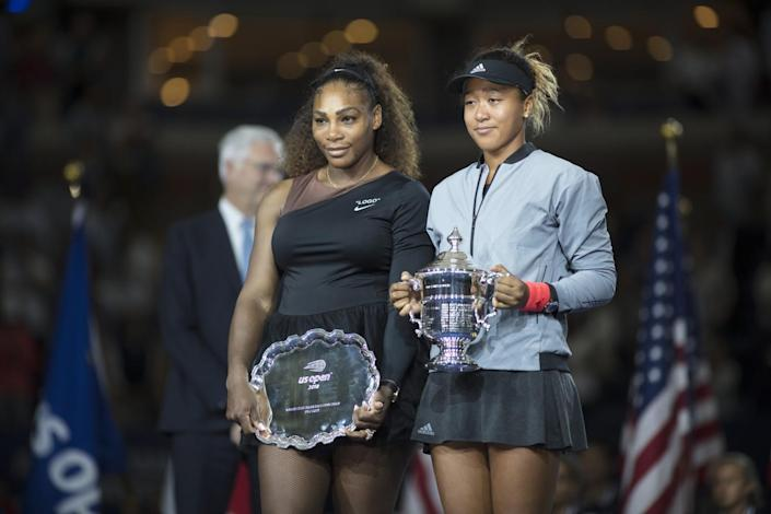 Two women in tennis uniforms stand side by side. The woman on the right holds a trophy, the other holds a silver platter.