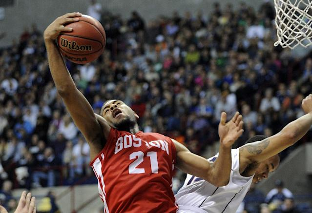 Boston University's Cedric Hankerson (21) fights for a rebound with Connecticut's Shabazz Napier during the first half of an NCAA college basketball game in Storrs, Conn., on Sunday, Nov. 17, 2013. (AP Photo/Fred Beckham)