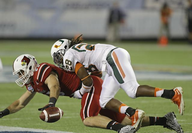 Miami defensive back Nantambu-Akil Fentress (28) breaks up a pass intended for Louisville tight end Ryan Hubbell, left, during the first half of the Russell Athletic Bowl NCAA college football game in Orlando, Fla., Saturday, Dec. 28, 2013. (AP Photo/John Raoux)