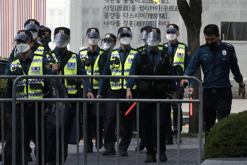 South Korean police officers wearing face masks and face shields to help protect against the spread of the coronavirus, walk in Seoul, South Korea, Saturday, Oct. 3, 2020. Seoul city temporarily banned outdoor rallies with 10 or more people over infection risks against the spread of the coronavirus. South Korea's new coronavirus daily tally has remained in two digits for a third straight day as authorities called for public vigilance during one of the country's biggest holidays. (AP Photo/Lee Jin-man)