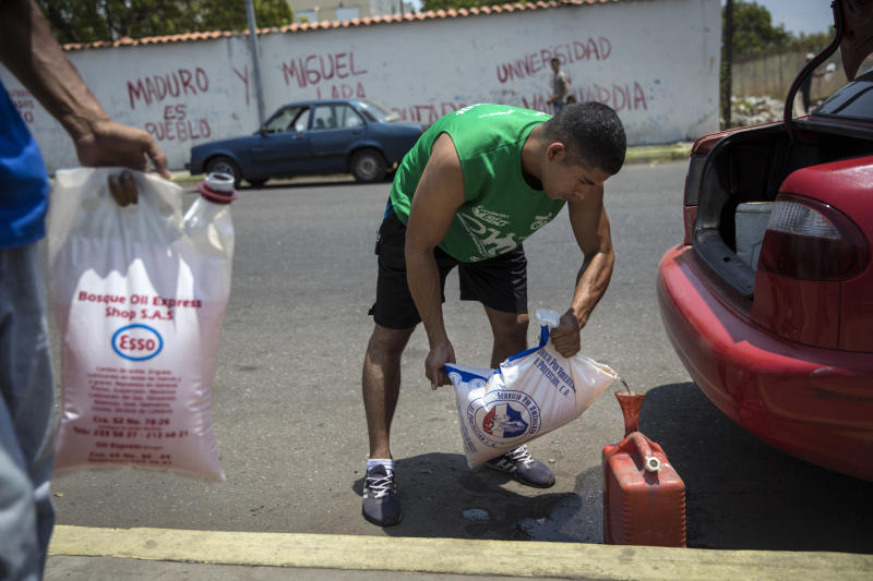 Jesus Gonzales fills a container with bagged gasoline he bought at extra cost at a fuel station, in order to not wait in the longer line in Cabimas, Venezuela, Saturday, May 18, 2019. U.S. sanctions on oil-rich Venezuela appear to be taking hold, resulting in mile-long lines for fuel in the South American nation's second-largest city, Maracaibo. (AP Photo/Rodrigo Abd)