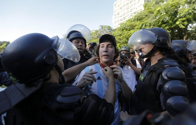 A demonstrator wears an Argentina national team jersey as he argues with policemen before the 2014 World Cup final match between Argentina and Germany in Rio de Janeiro, July 13, 2014. REUTERS/Marco Bello (BRAZIL - Tags: POLITICS SOCCER CRIME LAW SPORT CIVIL UNREST WORLD CUP)