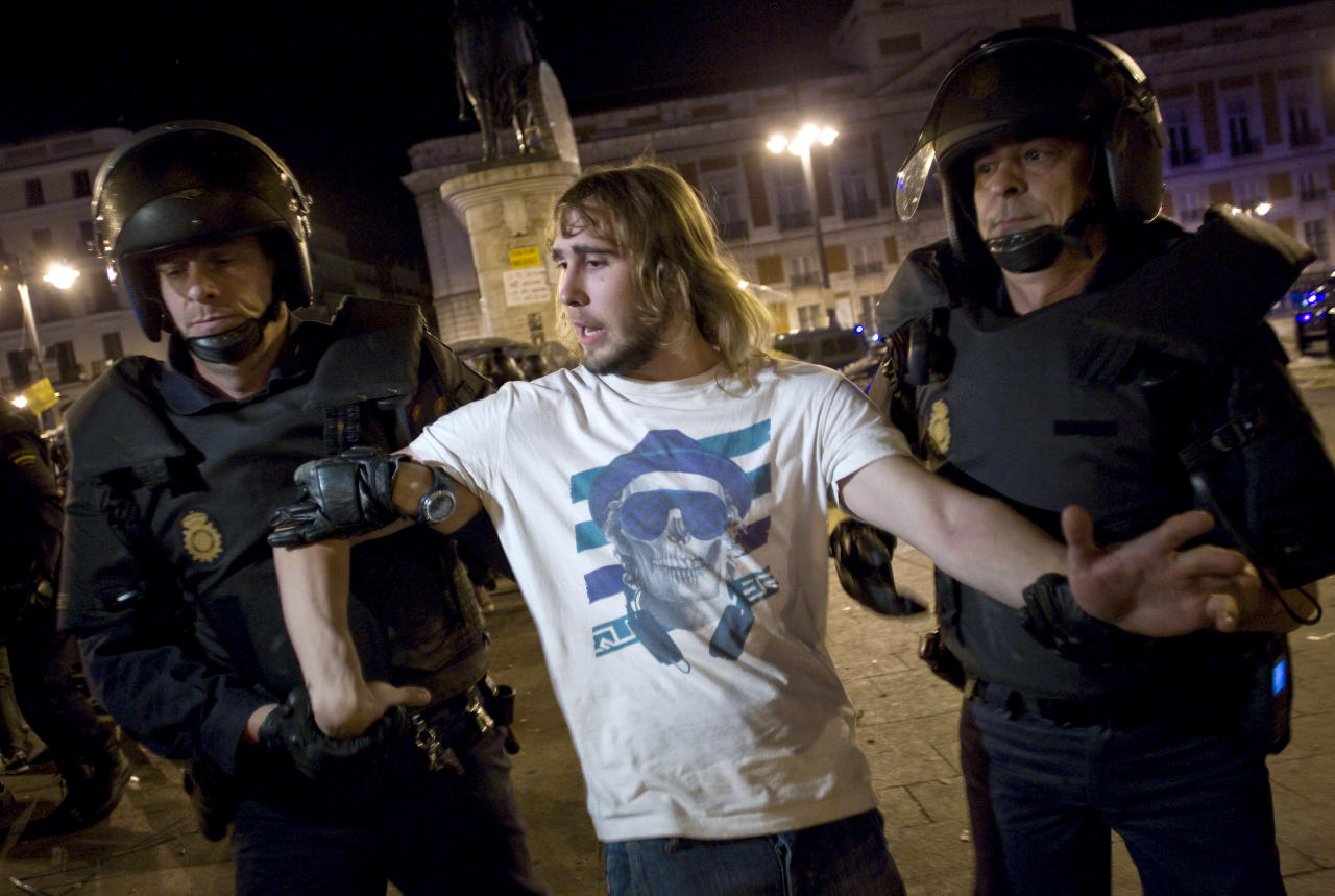 A demonstrator is led away by police officers as he and others are evicted from Puerta del Sol plaza in Madrid, Spain, during the early hours of Sunday, May 13, 2012. Spaniards angered by increasingly grim economic prospects and unemployment hitting one out of every four citizens protested in droves in the nation's largest cities, marking the one-year anniversary of a spontaneous movement that inspired similar anti-authority demonstrations across the planet. (AP Photo/Alberto Di Lolli)