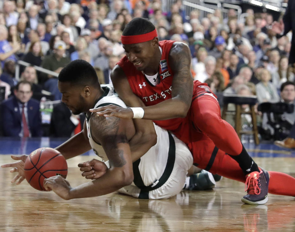 Michigan State forward Nick Ward, left, picks up a loose ball in front of Texas Tech forward Tariq Owens during the first half in the semifinals of the Final Four NCAA college basketball tournament, Saturday, April 6, 2019, in Minneapolis. (AP Photo/David J. Phillip)
