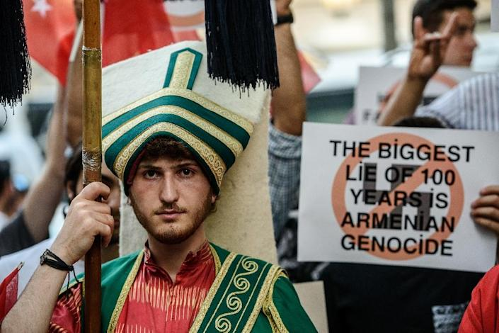 A Turkish nationalist protester wearing Ottoman clothes holds placard during a protest against Germany in front of the Germany consulate in Istanbul (AFP Photo/Ozan Kose)