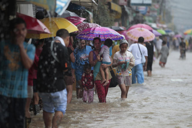 Families evacuate to higher ground after floodwaters caused by a swollen river surround their homes in Marikina city, east of Manila, Philippines on Tuesday, Aug. 20, 2013. Some of the Philippines' heaviest rains on record fell for a second day Tuesday, turning the capital's roads into rivers and trapping tens of thousands of people in homes and shelters. The government suspended all work except rescues and disaster response. (AP Photo/Aaron Favila)