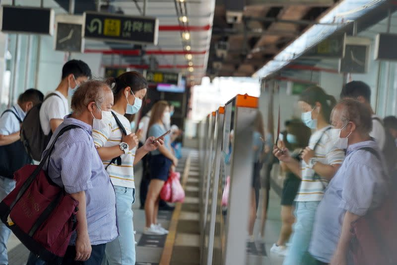 People wait for the train at a subway station in Hong Kong