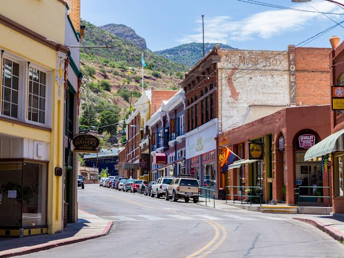 A street lined with cars and shops in Bisbee, arizona with mountains in the background