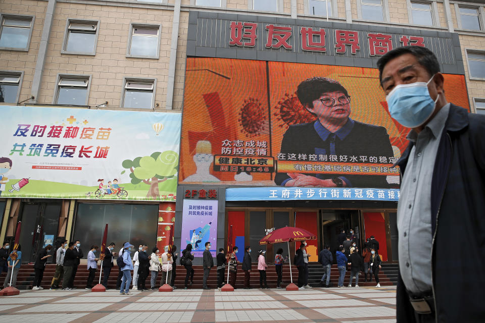 """A man wearing a face mask to help curb the spread of the coronavirus walks by masked residents lining up for COVID-19 vaccine at a coronavirus vaccination site with a board displaying the slogan, """"Timely vaccination to build the Great Wall of Immunity together"""" in Beijing, Wednesday, April 21, 2021. (AP Photo/Andy Wong)"""