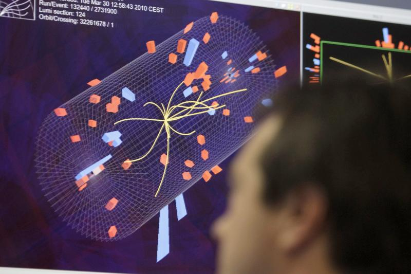 """FILE - In this March 30, 2010 file photo a scientist looks at the pictures of the first collisions at full power at the CMS experience control room at the European Organisation for Nuclear Research (CERN) in Meyrin near Geneva, Switzerland. The head of the world's biggest atom smasher is claiming discovery of a new particle that he says is consistent with the long-sought Higgs boson known popularly as the """"God particle"""" which is believed to give all matter in the universe size and shape. (AP Photo/Keystone/Salvatore Di Nolfi, File)"""