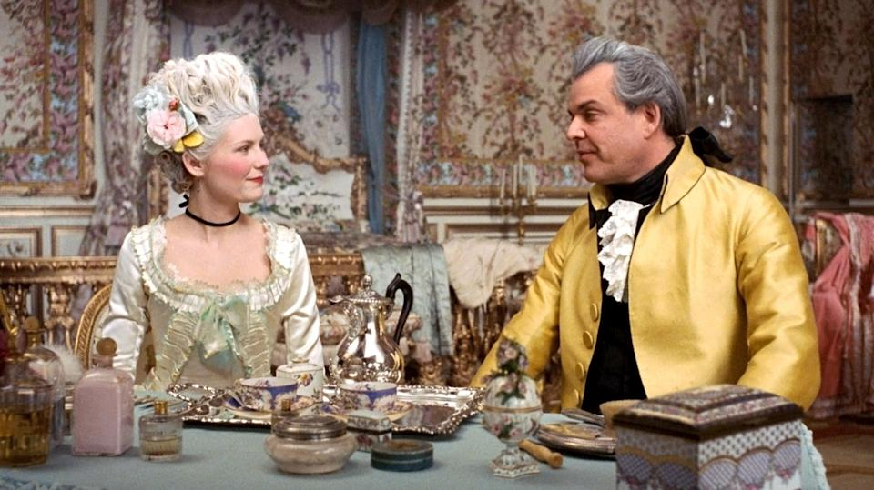Kirsten Dunst and Danny Huston sit at tea wearing prerevolution French finery