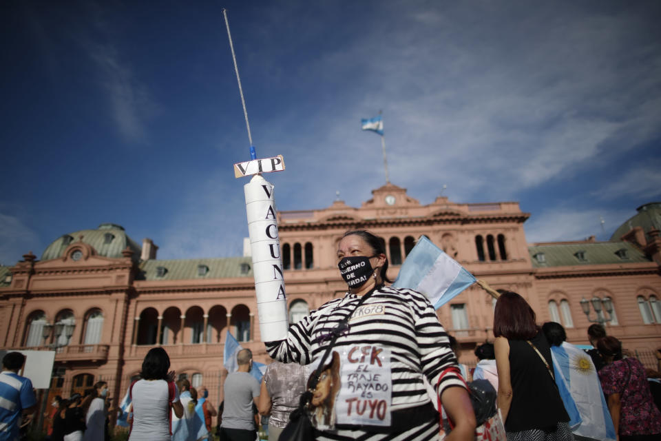 FILE - In this Feb. 27, 2021 file photo, a demonstrator holds an object representing a syringe during a protest against the government of President Alberto Fernandez and its handling of the COVID-19 vaccines, in Buenos Aires, Argentina. The South American country recorded on Wednesday, July 14, 2021, more than 100,000 deaths from the virus since the pandemic began. (AP Photo/Natacha Pisarenko, File)
