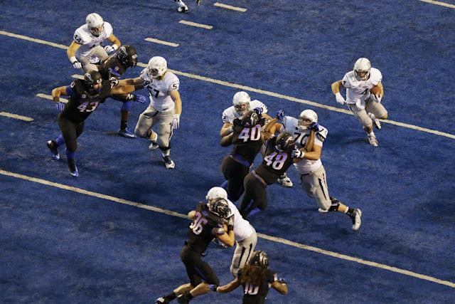 Nevada's Kendall Brock, upper right, begins a touchdown run as offensive linesman Joel Bitonio (70) blocks Boise State defensive end Kharyee Marshall (48) in the first half of an NCAA college football game, Saturday, Oct. 19, 2013 in Boise, Idaho. (AP Photo/Ted S. Warren)