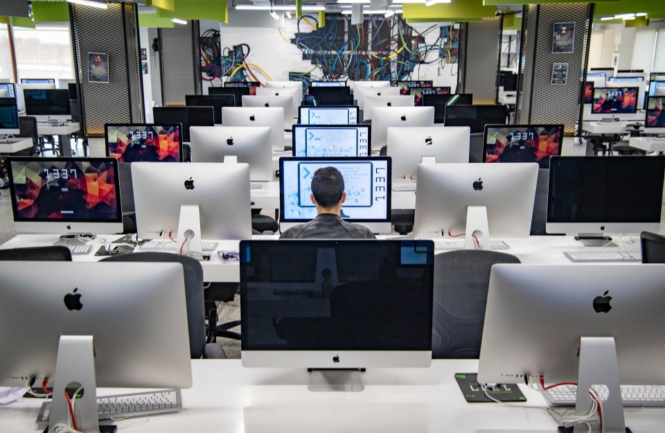 """A student, mask-clad due to the COVID-19 coronavirus pandemic, uses a computer at a lab room at the """"1337"""" information technology training centre in Morocco's central city of Khouribga on November 17, 2020. - With its rows of sleek computers and ultra-modern study methods, Morocco's 1337 campus is a dream come true for budding geeks, in a country where IT skills are in high demand. Conceived as a paradise for coders, the centre offers project-based training on programming, innovation and building IT systems. Tuition is free and students largely create their own curricula. (Photo by FADEL SENNA / AFP) (Photo by FADEL SENNA/AFP via Getty Images)"""