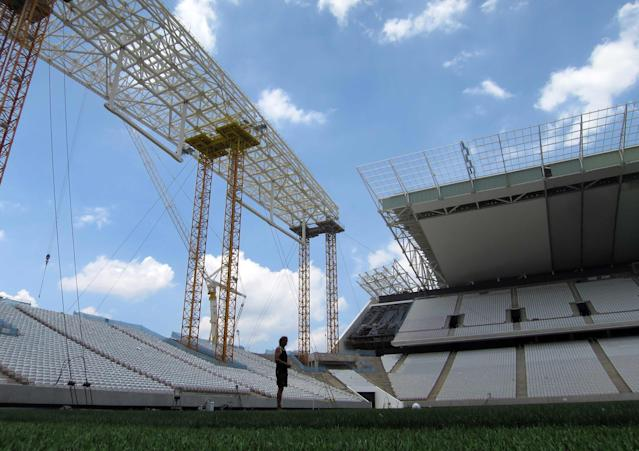 """A workman installing grass in the Arena Sao Paulo stadium, known as """"Itaquerao"""" stands on the pitch as construction continues in Sao Paulo December 8, 2013. Damage to the roof from last month's crane collapse can be seen in the center of the photo. The stadium will host the opening match of the 2014 FIFA World Cup soccer championship. REUTERS/Gary Hershorn (BRAZIL - Tags: SPORT SOCCER WORLD CUP)"""
