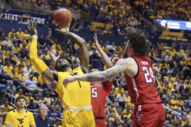 West Virginia forward Derek Culver (1) goes to shoot as he is defended by Texas Tech guards Kevin McCullar (15) and Avery Benson (24) during the second half of an NCAA college basketball game Saturday, Jan. 11, 2020, in Morgantown, W.Va. (AP Photo/Kathleen Batten)