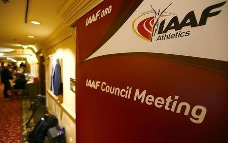FILE PHOTO - Journalists are seen near a logo of the International Association of Athletics Federations (IAAF) at a hotel where the IAAF council holds a meeting in Vienna, Austria, June 17, 2016. REUTERS/Leonhard Foeger