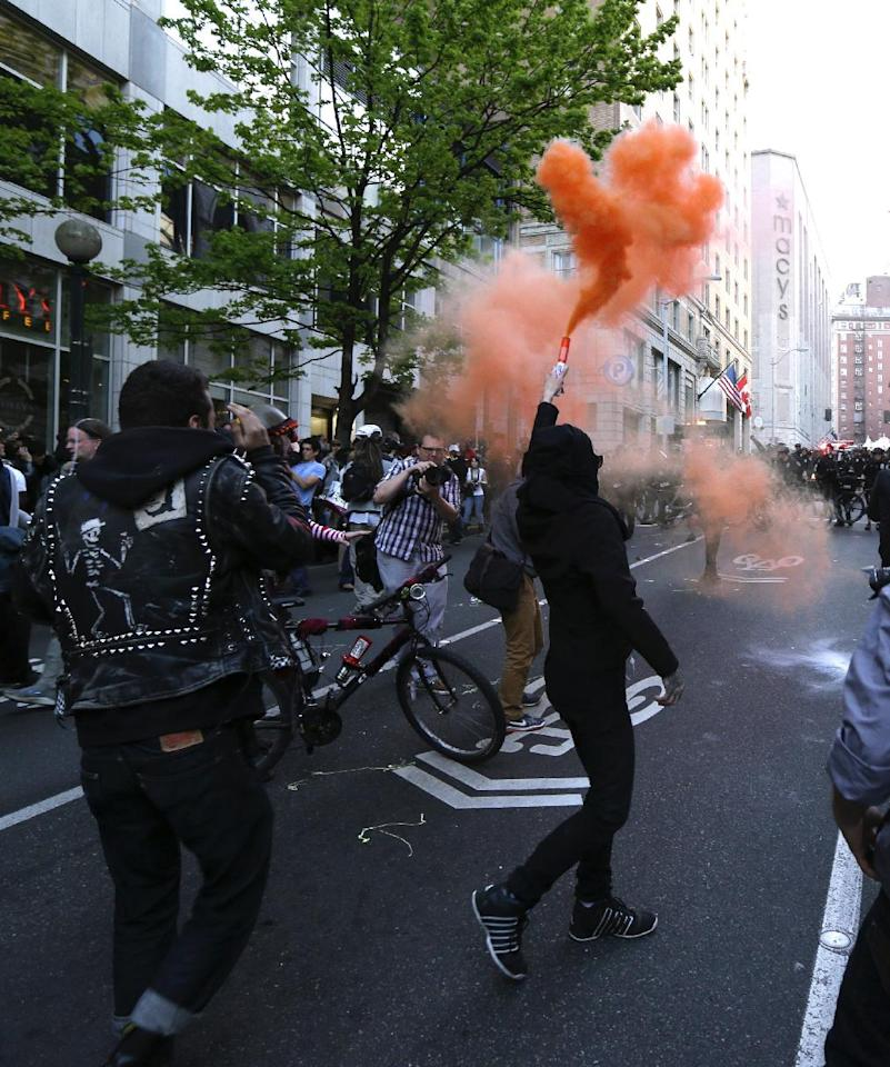 A protester waves a smoke device during a May Day march that began as an anti-capitalism protest and turned into demonstrators clashing with police, Wednesday, May 1, 2013, in downtown Seattle. (AP Photo/Ted S. Warren)