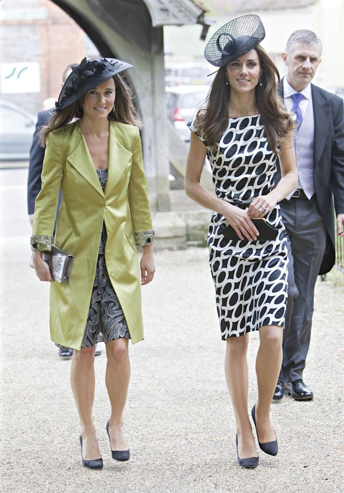 <p>Just two months after her own big day, the Duchess attended the wedding of friends Sam Waley-Cohen and Annabel Ballin with sister Pippa in tow. The royal wore an understated look for the occasion so not to overshadow the bride: a monochrome shift dress from Zara paired with a black hat. <em>(Photo: PA)</em> </p>