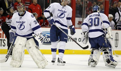 Tampa Bay Lightning goalie Dwayne Roloson (30) exits the ice briefly as goalie Sebastien Caron (35) enters the game in the second period of an NHL hockey game against the New Jersey Devils, Thursday, March 29, 2012, in Newark, N.J. Roloson came back into the ice before the puck was dropped to restart the play. (AP Photo/Julio Cortez)