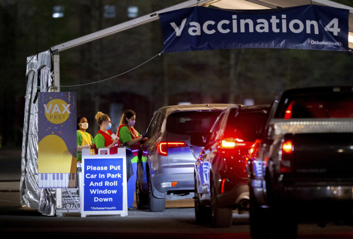 Ochsner nurses and volunteers give a Moderna COVID-19 vaccine at 5 a.m. during the 24-hour Max Fest at the Shrine on Airline in Metairie near New Orleans, Tuesday, March 30, 2021. Anyone who does not have an appointment can show up and get a vaccine until 7 a.m. Louisiana is making a full-court press to get shots in arms, with sometimes creative outreach to make it as easy as possible to get vaccinated. (David Grunfeld/The Times-Picayune/The New Orleans Advocate via AP)