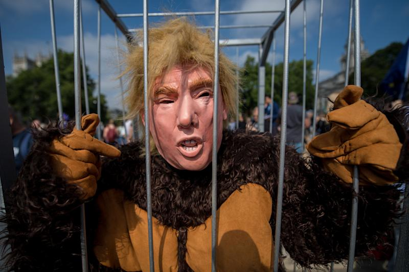 A man dressed asTrump in a gorilla costume stands in what appears to be a prison cell during a London protest.