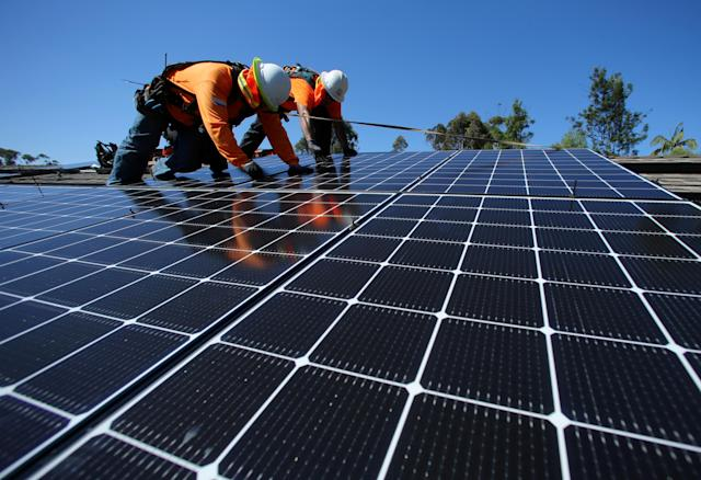 Installers place solar panels on the roof of a residence in San Diego, Calif. (Photo: Mike Blake/Reuters)