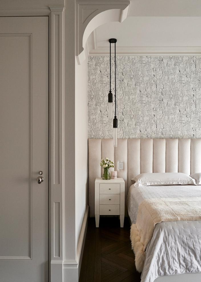 "<div class=""caption""> A channel-tufted custom headboard in the master suite's sleeping alcove softens the distressed paint design of the wallpaper from <a href=""https://www.blackedition.com"" rel=""nofollow noopener"" target=""_blank"" data-ylk=""slk:Black Edition"" class=""link rapid-noclick-resp"">Black Edition</a>. The pendant lights are from <a href=""https://apparatusstudio.com/"" rel=""nofollow noopener"" target=""_blank"" data-ylk=""slk:Apparatus Studio"" class=""link rapid-noclick-resp"">Apparatus Studio</a>. </div>"