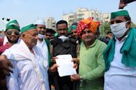 Bharatiya Kisan Union (BKU) members are seen handing over a letter with their demands to Kumar Ranvijay, Additional DCP, Noida at the Delhi-Noida border in protest against the farms bills passed by Modi government on September 25, 2020 in Noida, India. Farmers from different villages gathered to march to Delhi as part of a nationwide protest all across the country. (Photo by Mayank Makhija/NurPhoto via Getty Images)