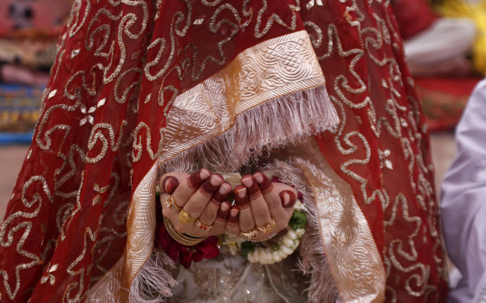 A Muslim bride prays while she attend last Friday prayer during the holy fasting month of Ramadan, at the historical Badshahi mosque, in Lahore, Pakistan, Friday, May 7, 2021. (AP Photo/K.M. Chaudary)