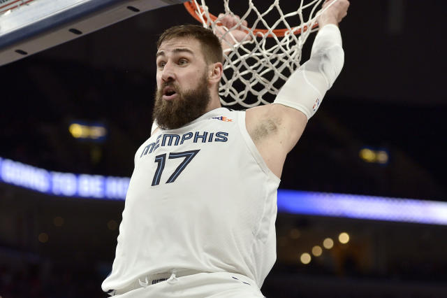 Memphis Grizzlies center Jonas Valanciunas (17) hangs from the rim after a dunk in the second half of an NBA basketball game against the Denver Nuggets Tuesday, Jan. 28, 2020, in Memphis, Tenn. (AP Photo/Brandon Dill)