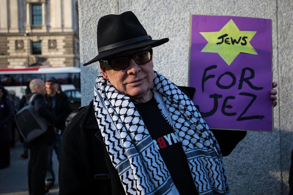 <em>A pro-Jeremy Corbyn protester holds a placard during a counter-protest to a demonstration in Parliament Square against anti-Semitism in the Labour Party (Getty)</em>