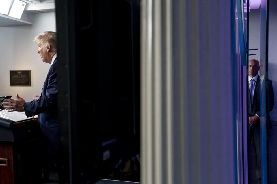 A member of the Secret Service stands guard, right, as President Donald Trump, left, speaks at a news conference in the James Brady Press Briefing Room at the White House, Monday, Aug. 10, 2020, in Washington. Trump briefly left because of a security incident outside the fence of the White House. (AP Photo/Andrew Harnik)