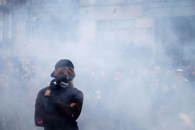 An activist stands amid smoke from a stun grenade while protesting in Washington, D.C., Jan. 20, 2017.