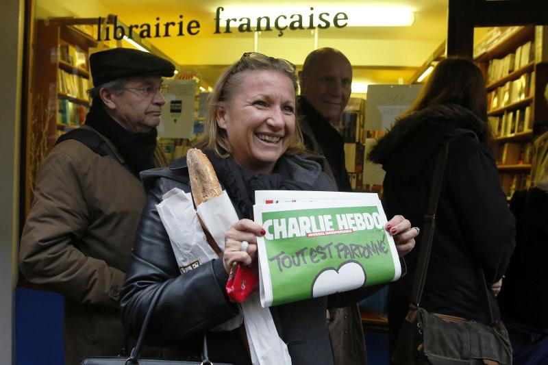 A woman poses with her copy of Charlie Hebdo as it goes on sale in London