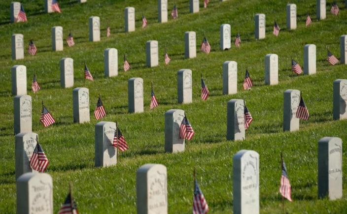 Flags are seen by military headstones at Los Angeles National Cemetery on Memorial Day in Los Angeles.