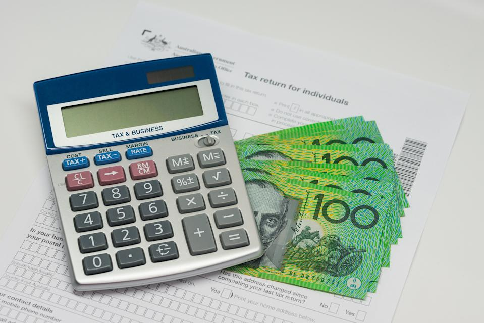 An image of a calculator, $100 bills and a tax return form.